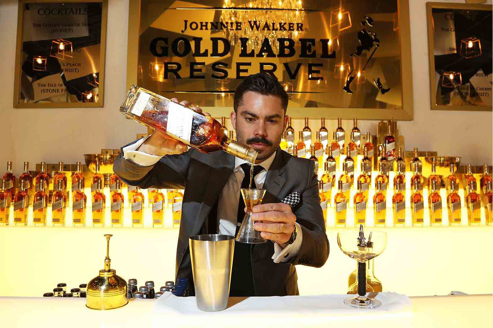 Bartender pouring whisky in a Johnnie Walker Gold Label Reserve bar