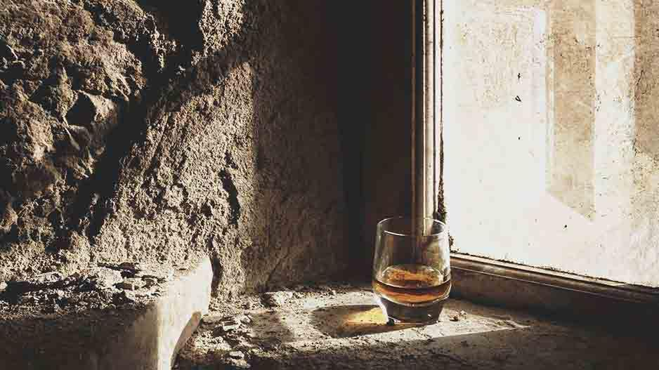 Glass of whisky on a stone window ledge