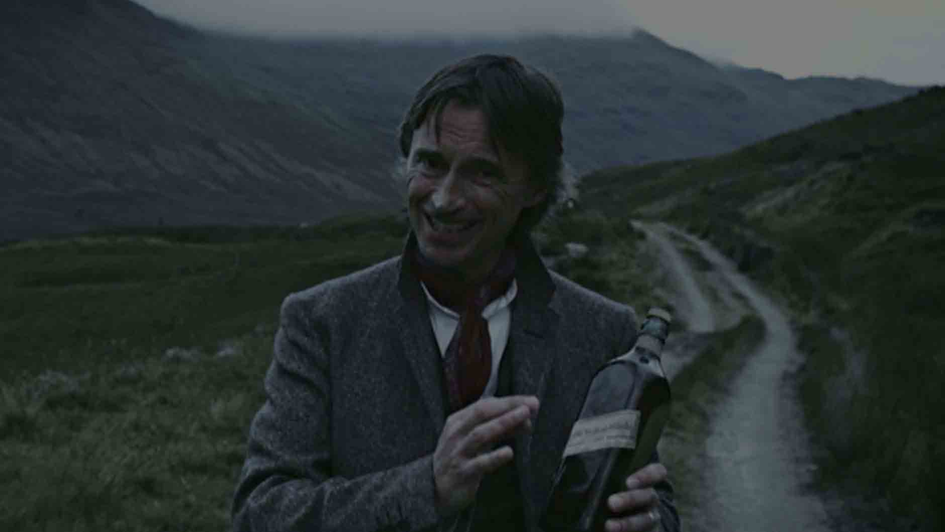 Robert Carlyle holding a bottle of Johnnie Walker whisky